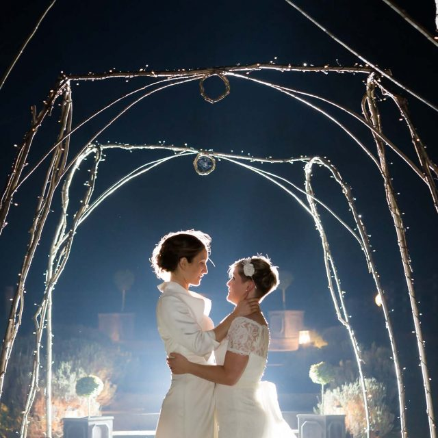 Brides embrace at the ned of their wedding day