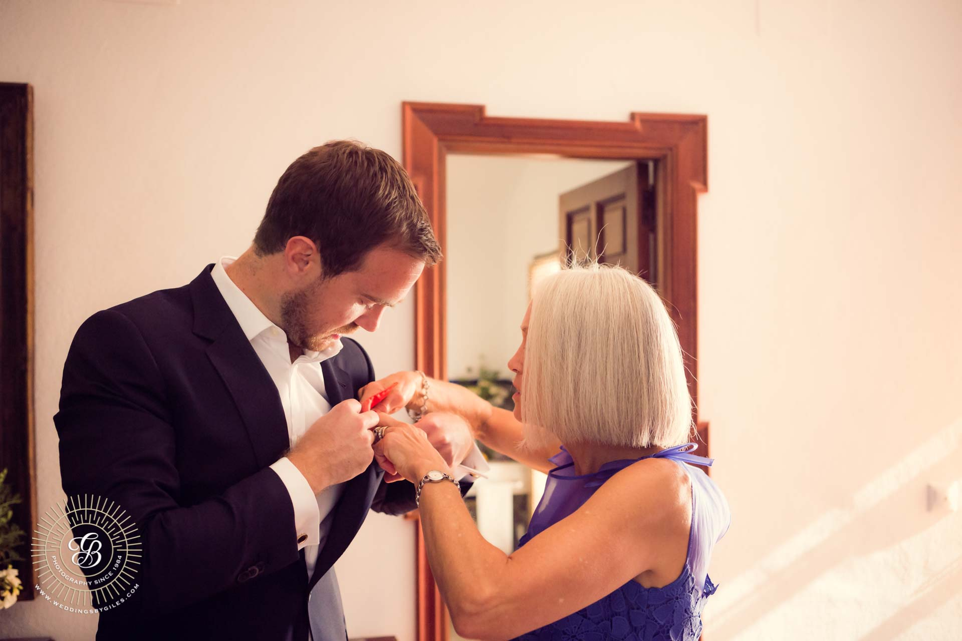 grooms mother adjusts his pocket square