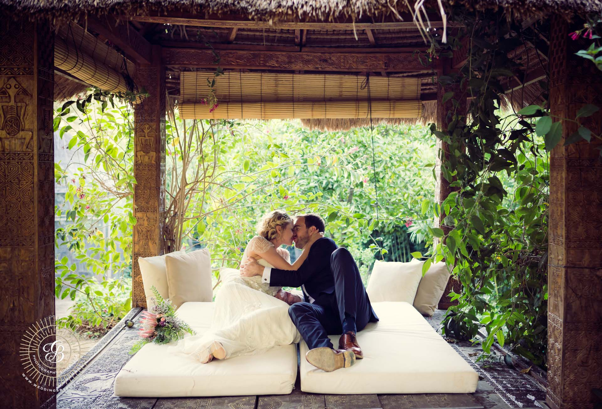 bride and groom kiss under pergola