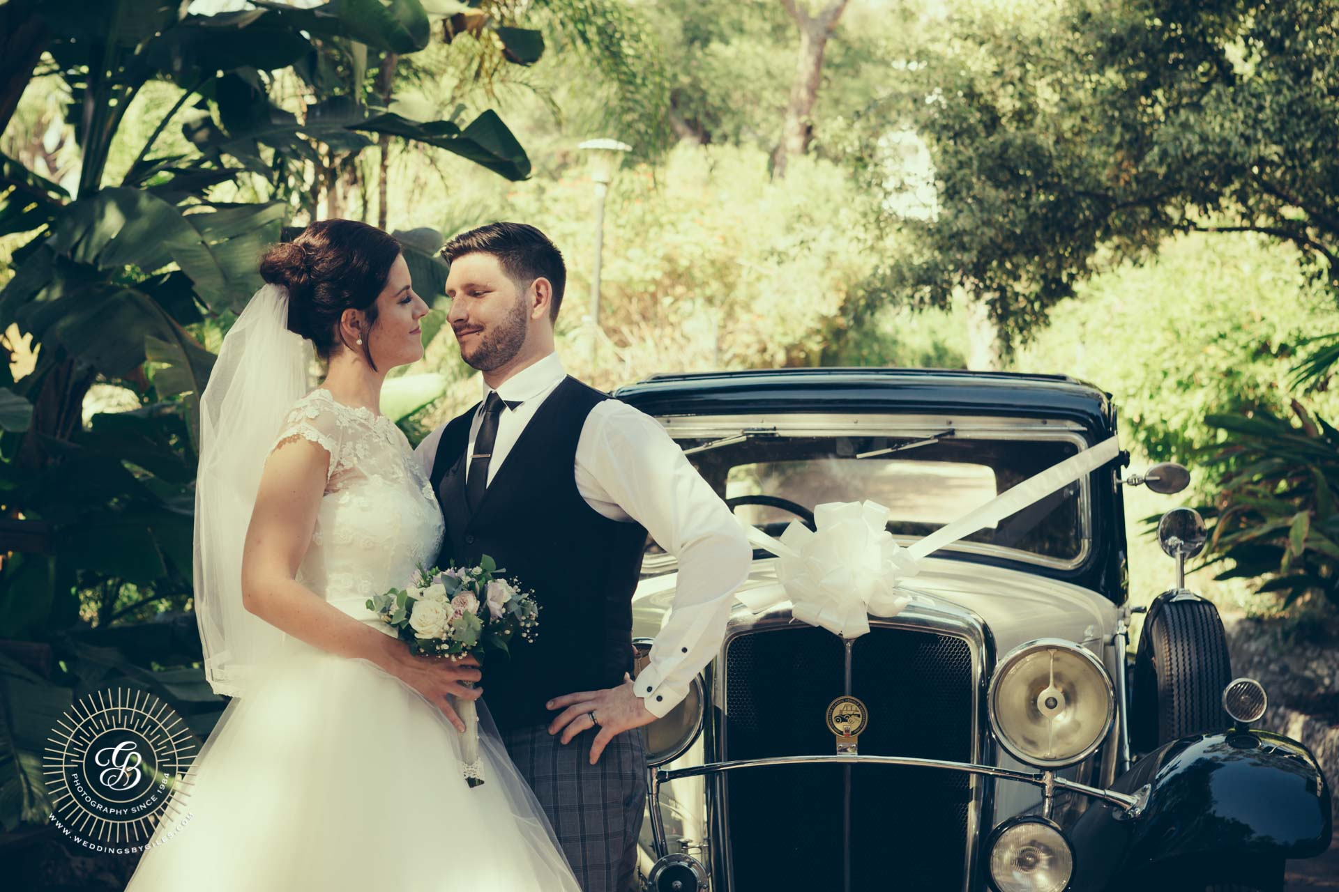 newlyweds and vintage wedding car