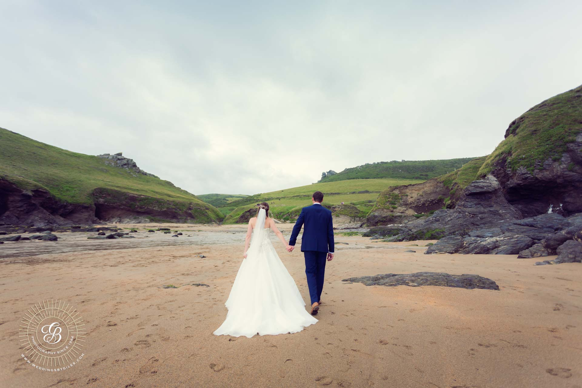 Bride and groom hand in hand on the beach