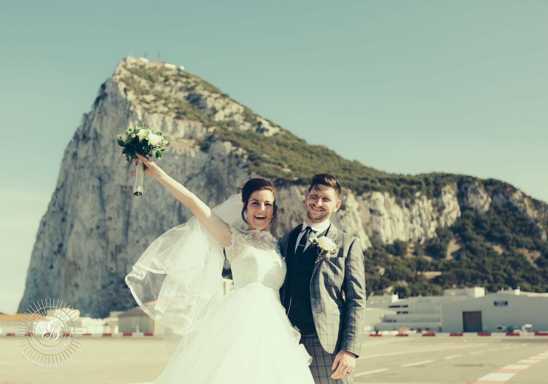 bride and groom in fron of the rock on the run way
