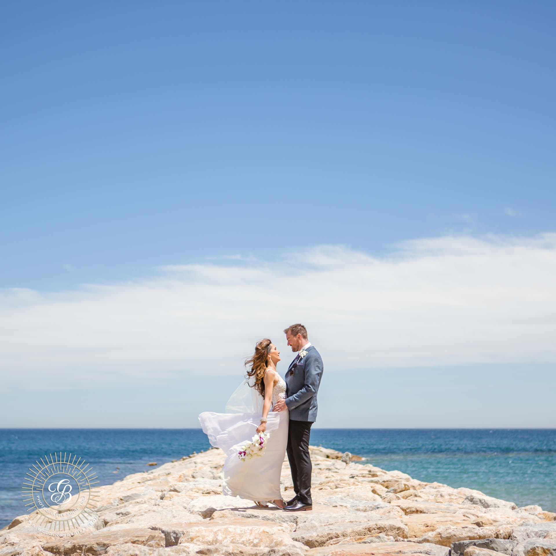 bride and groom embrace over the mediterranean