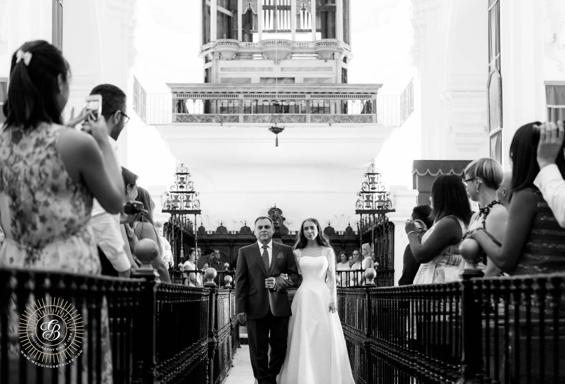 bride comes down the isle In catholic church wedding