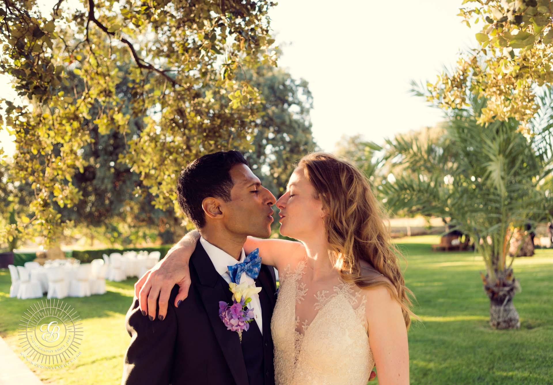 lovers kiss at garden wedding in spain