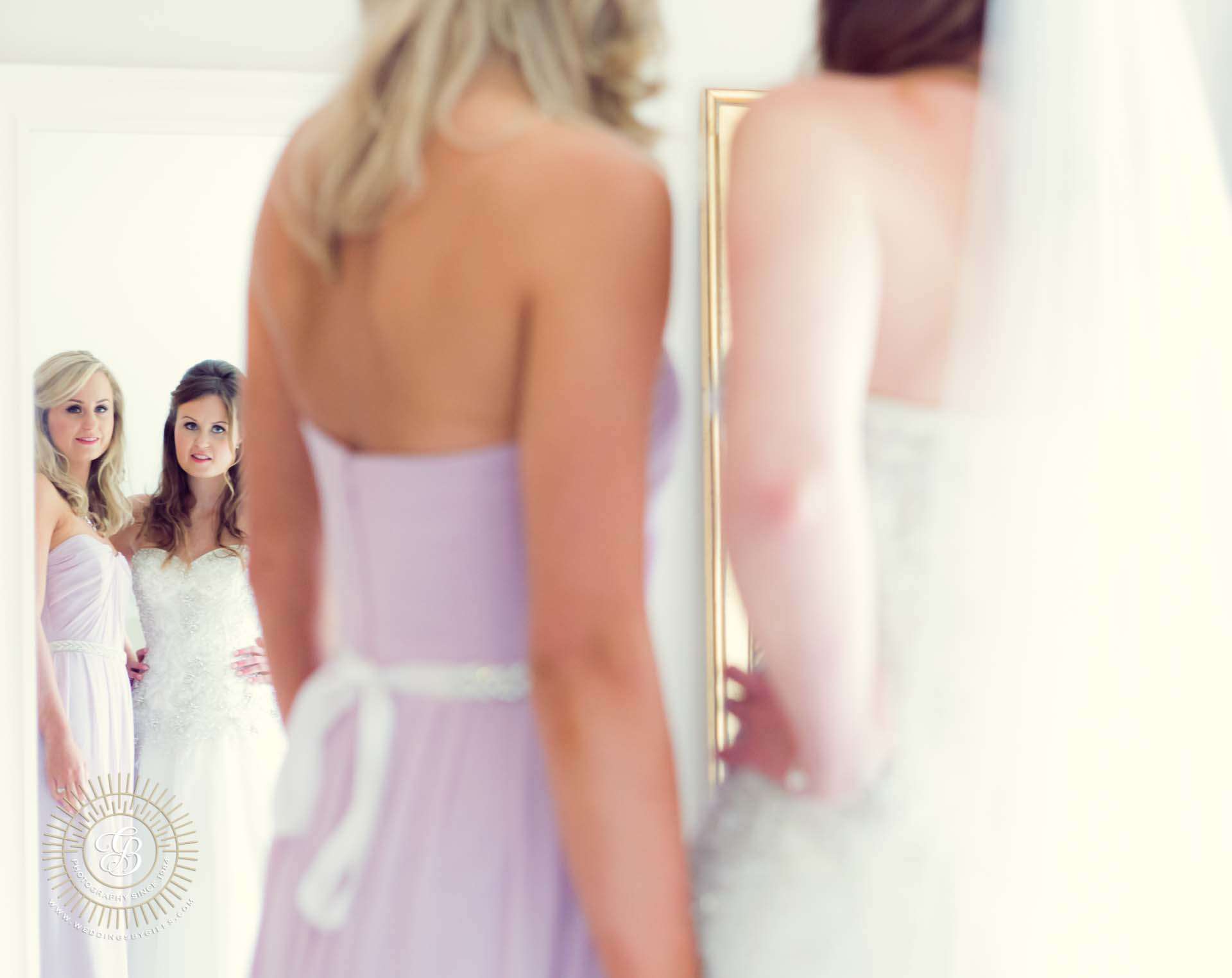 Bride and her sister bridesmaid look in the mirror
