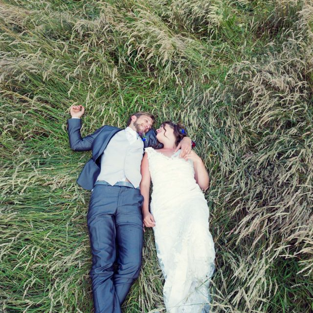 Bride and groom lie in long grass