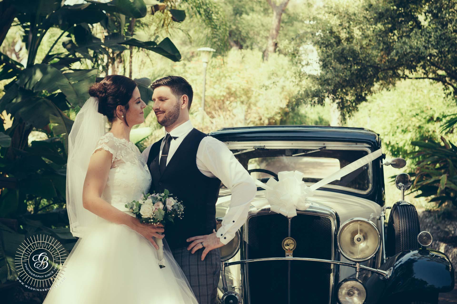 newlyweds and vintage wedding car
