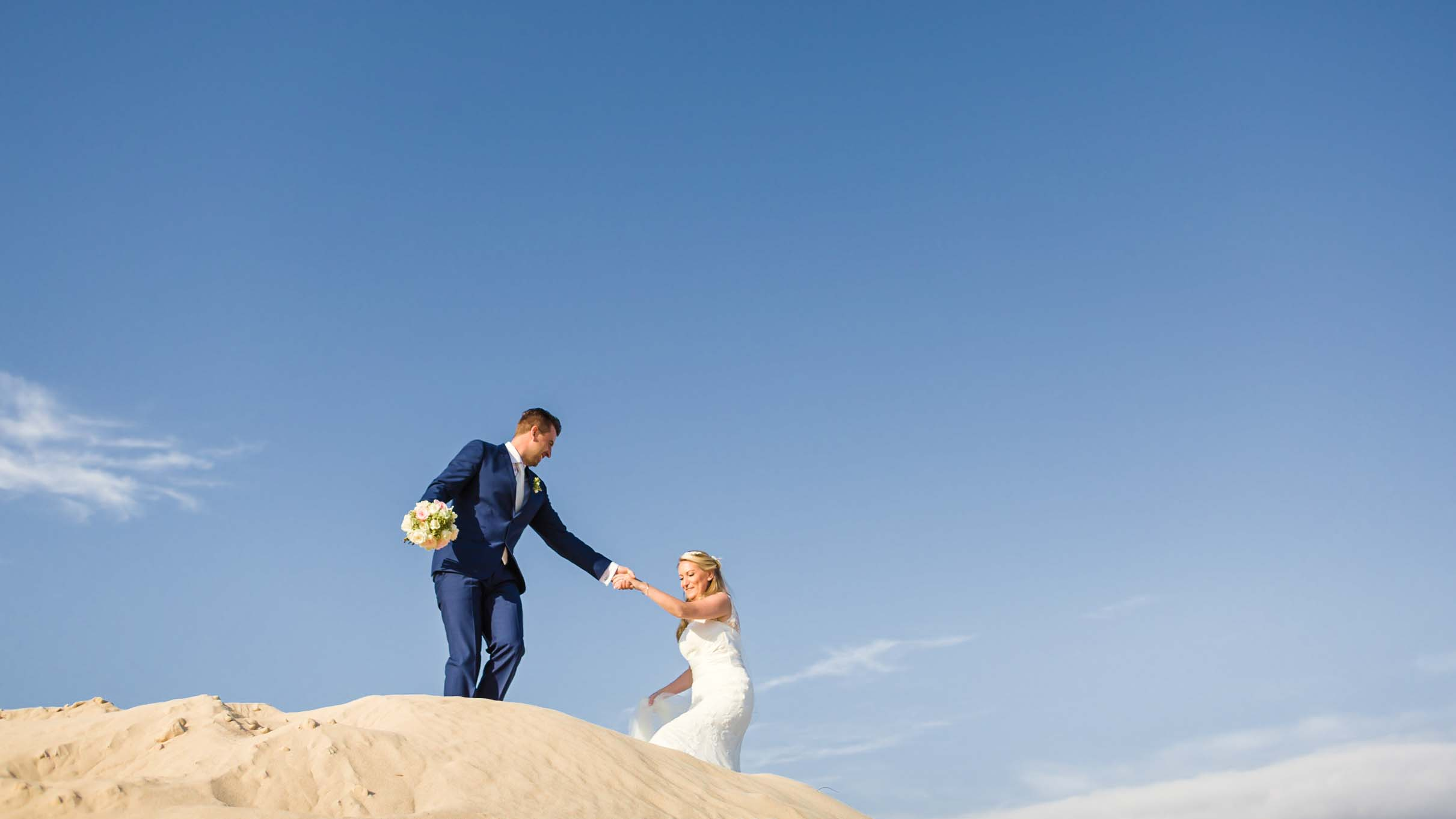 bride and groom hand in hand on sand dunes