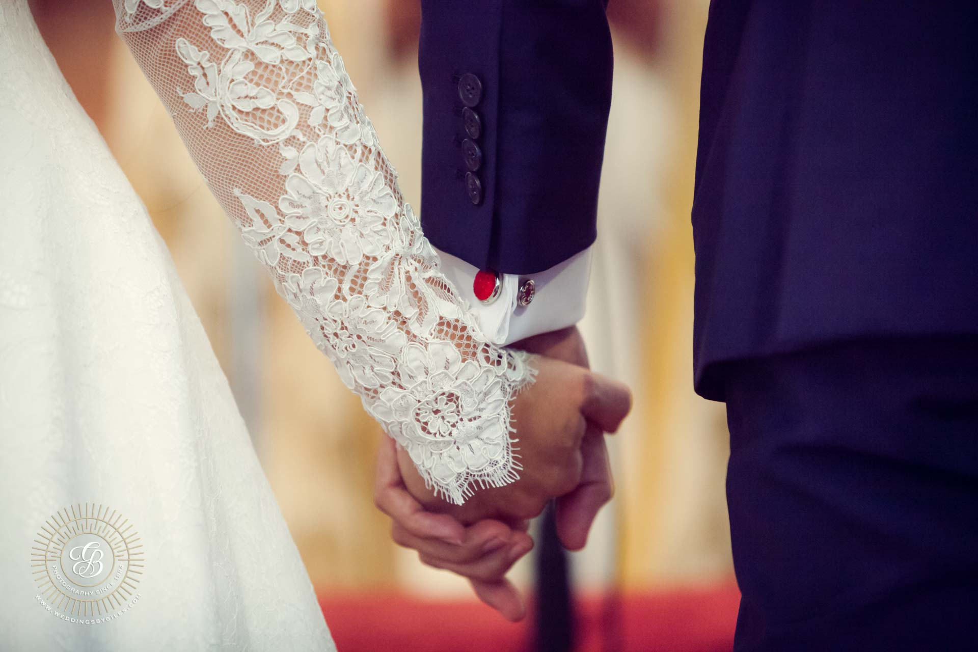 bride and groom hold hands in church