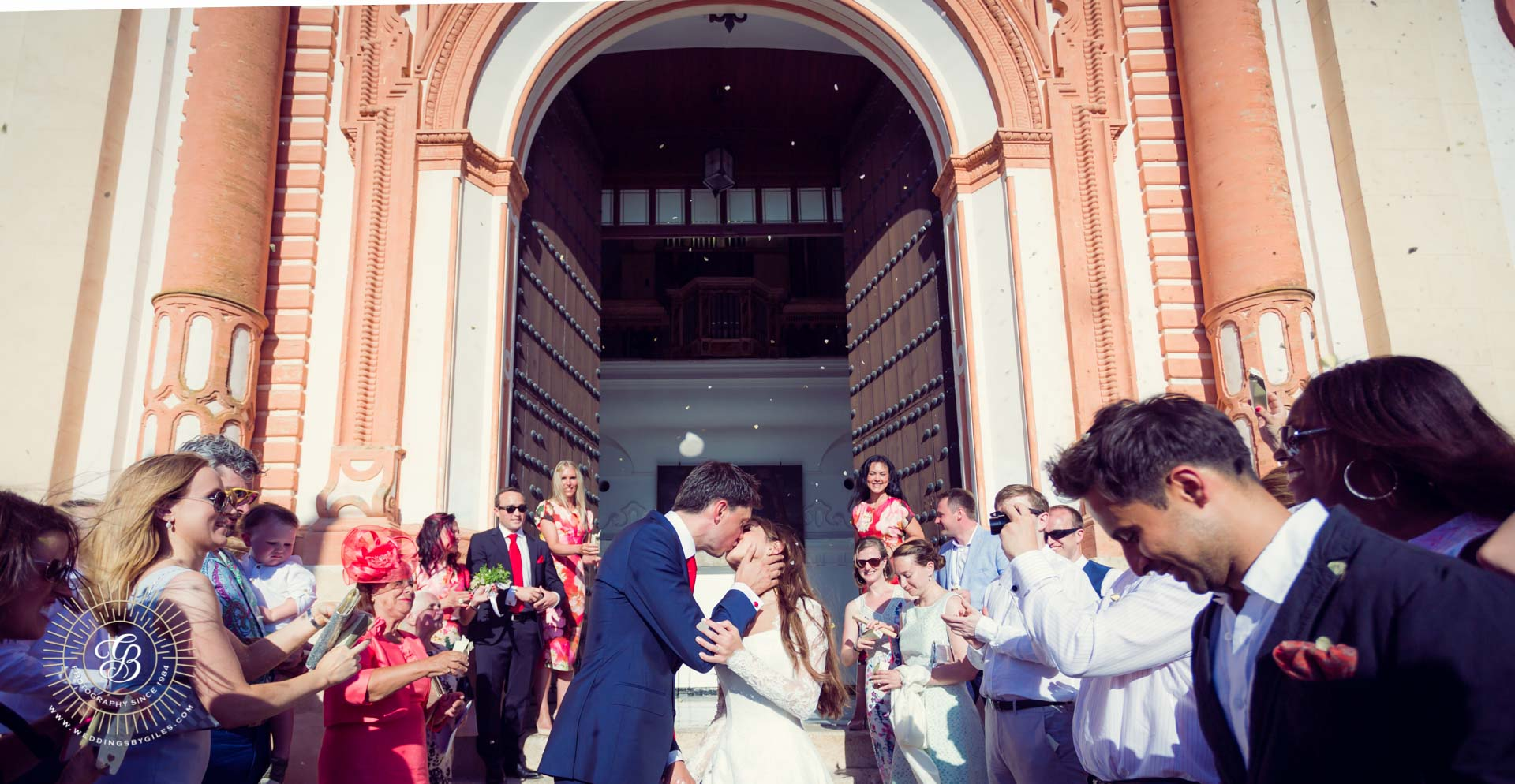 kiss under confetti out side the church