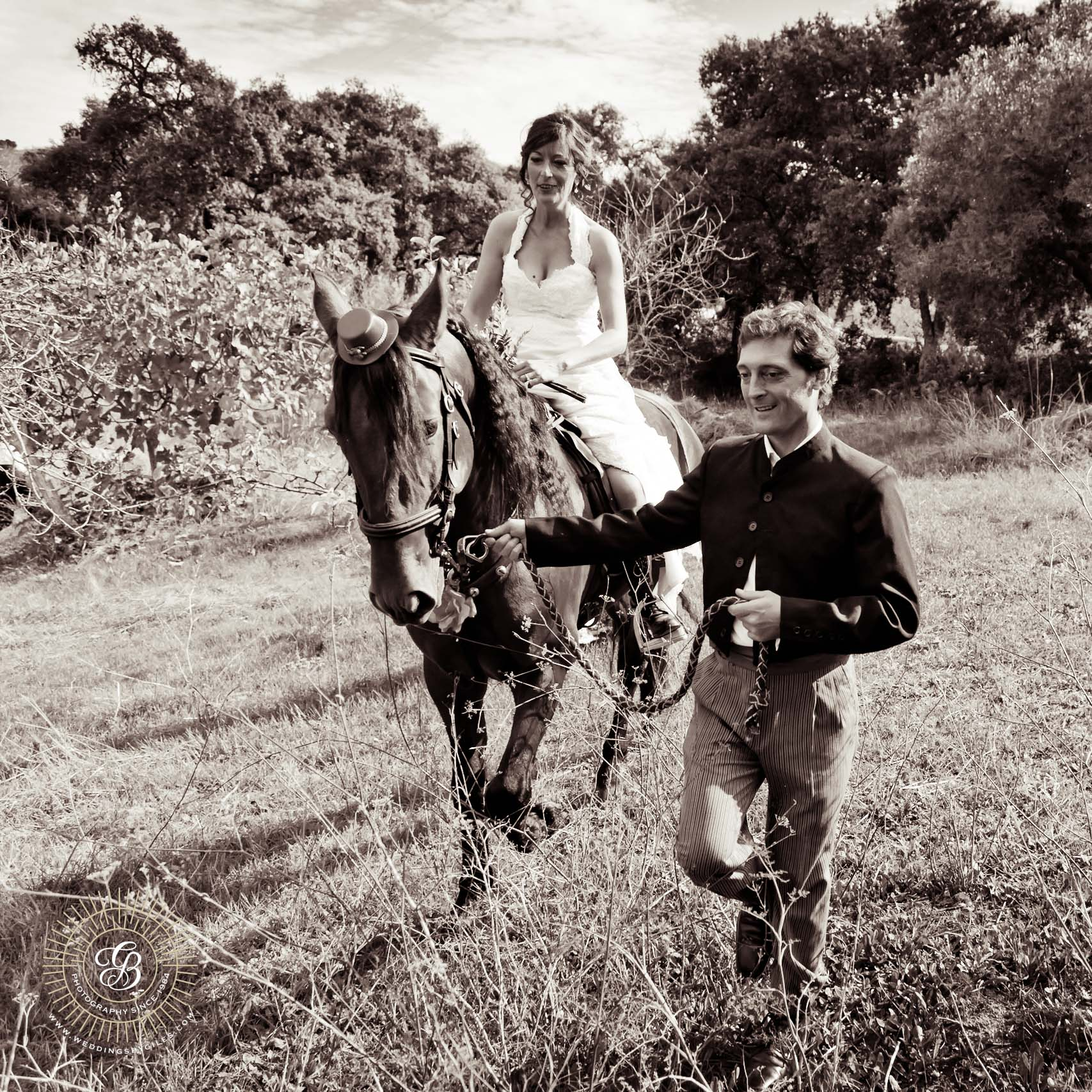 Groom leads his bride accross the fields