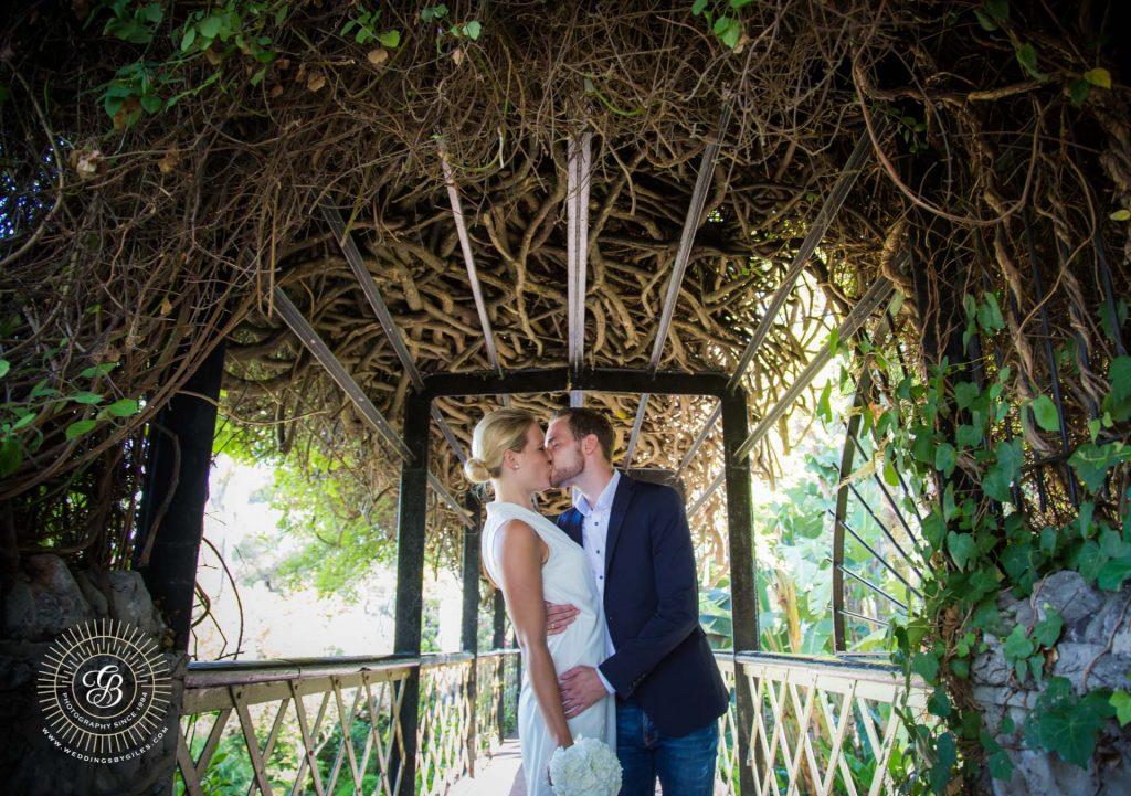 bride and groom kiss on the bridge