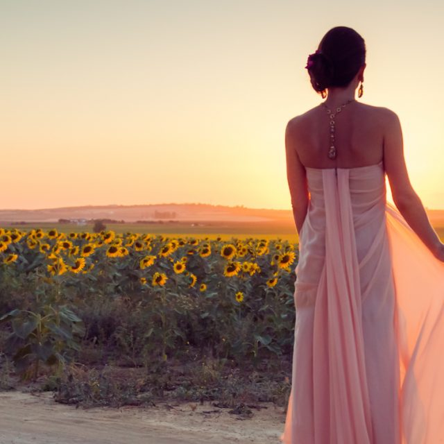 Bride looking out over sunflower fields at sunset